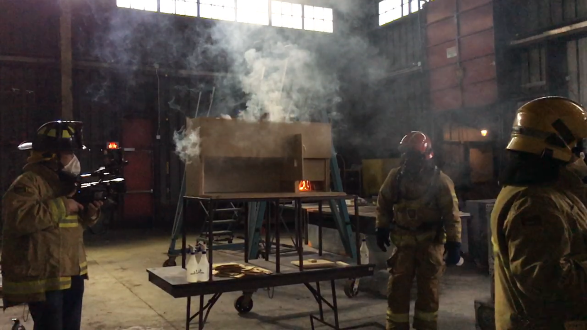 "A group of firefighters practicing fire behavior with a complex ""dollhouse"" model."