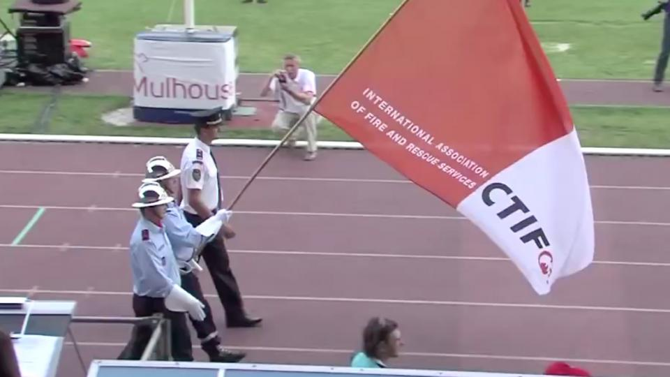 Firefighters holding the official flag of CTIF on a sports arena