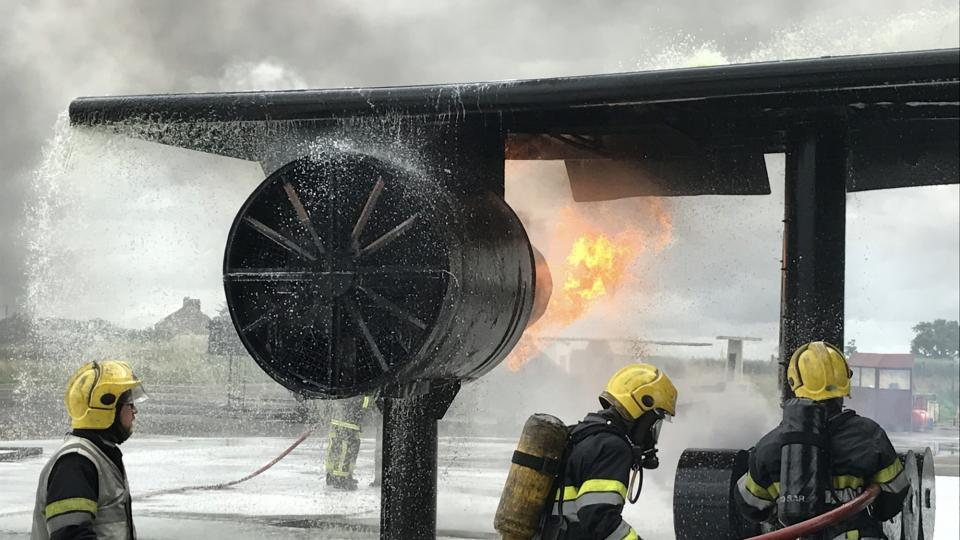 Firefighters practicing fighting an airplane fire