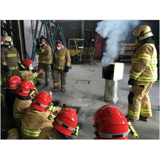 A group of firefighters watching instructor Shan Raffel demonstrate a single compartment dollhouse burn.